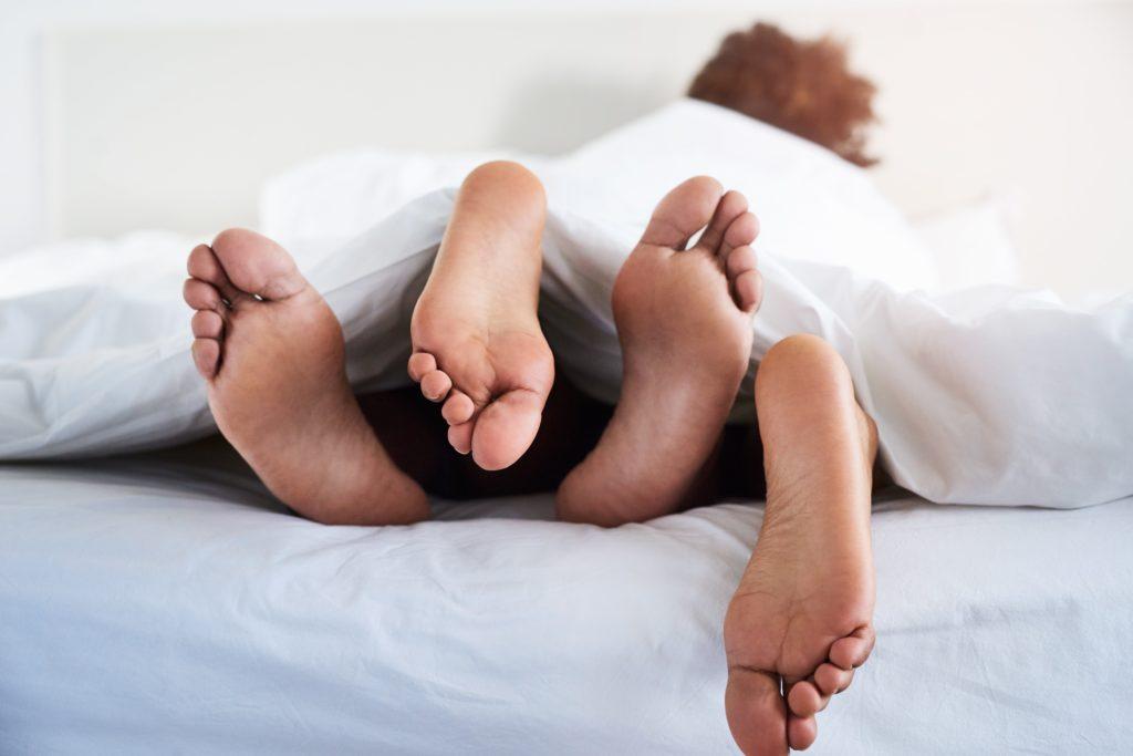 Jong koppel intiem in bed. Voor een goed libido en voortplanting moeten je sekshormonen in balans zijn.