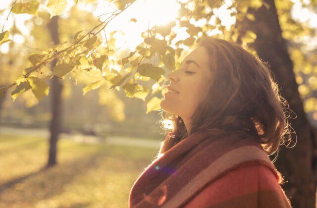 vrouw staat in de zon en doet vitamine d op